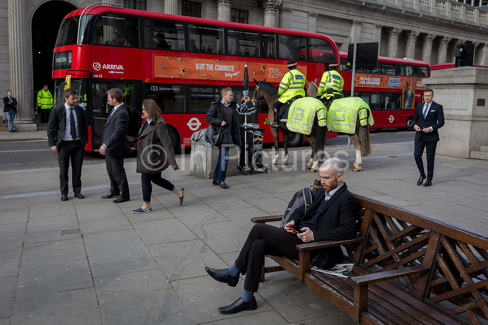 Two officers on horses with the mounted City Police, patrol Conhill and the Bank of England, in the City of London, the capitals financial district, on 14th March 2018, in London England.