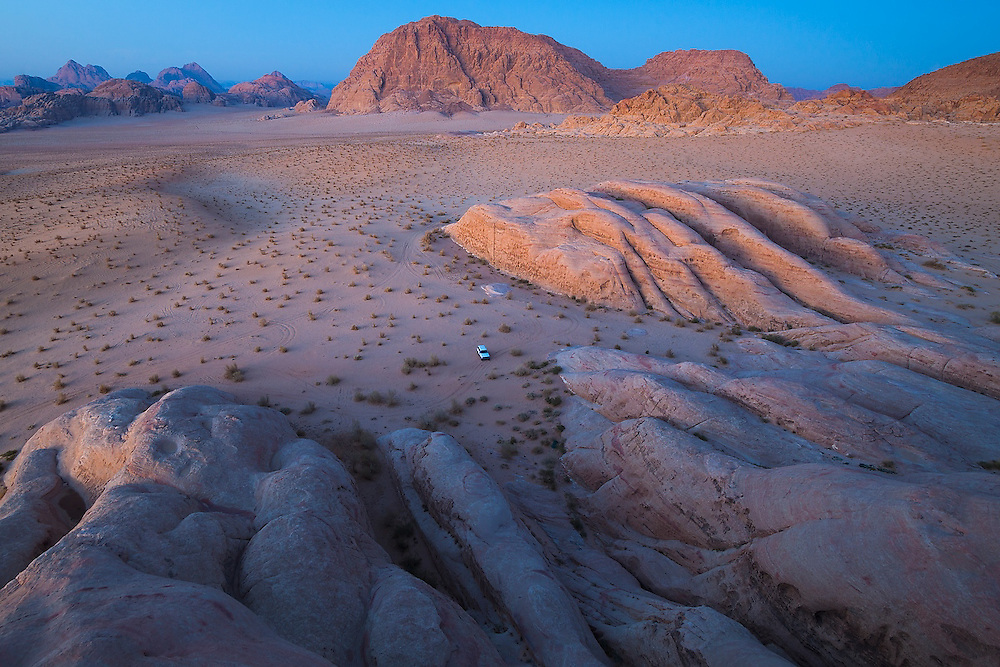 A jeep is parked at the base of pink sandstone formations at dusk in Wadi Rum, Jordan.