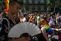 A young man dressed in a Japanese kimono and using a fan on the boulevard St Michel at the Paris Gay Pride in July 2019.