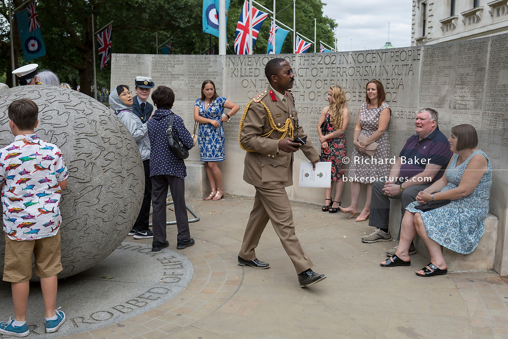 On the 100th anniversary of the Royal Air Force (RAF) and following a flypast of 100 aircraft formations representing Britain's air defence history which flew over central London, a Kenyan officer leaves Horseguards, passing the memorial to those killed in the 2002 Bali bombing, on 10th July 2018, in London, England.