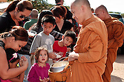 """24 OCTOBER 2010 - CHANDLER, AZ: Ajahn RAYWAT collects rice during the """"tak bat"""" or donation of rice to the monks, an important part of Buddhist merit making, during the Ok Phansa services to mark the end of Buddhist Lent at Wat Pa, in Chandler, AZ, Sunday October 24. Buddhist Lent is a time devoted to study and meditation. Buddhist monks remain within the temple grounds and do not venture out for a period of three months starting from the first day of the waning moon of the eighth lunar month (in July) to the fifteenth day of the waxing moon of the eleventh lunar month (in October). Ok Phansa Day marks the end of the Buddhist lent and falls on the full moon of the eleventh lunar month, this year Oct 23. Wat Pa, a Thai Theravada Buddhist temple, celebrated Ok Phansa Day on October 24.    Photo by Jack Kurtz"""