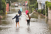 A group of college students play on Water Street in the historic district flooded as Hurricane Joaquin brings heavy rain, flooding and strong winds as it passes offshore October 4, 2015 in Charleston, South Carolina.