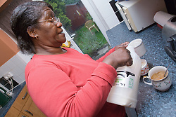 Older woman in her kitchen pouring milk into a cup of coffee,