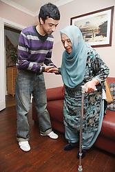 South Asian son helping his mother get up from sofa.