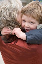 Grandmother hugging young boy,