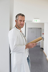Portrait of doctor with file, smiling
