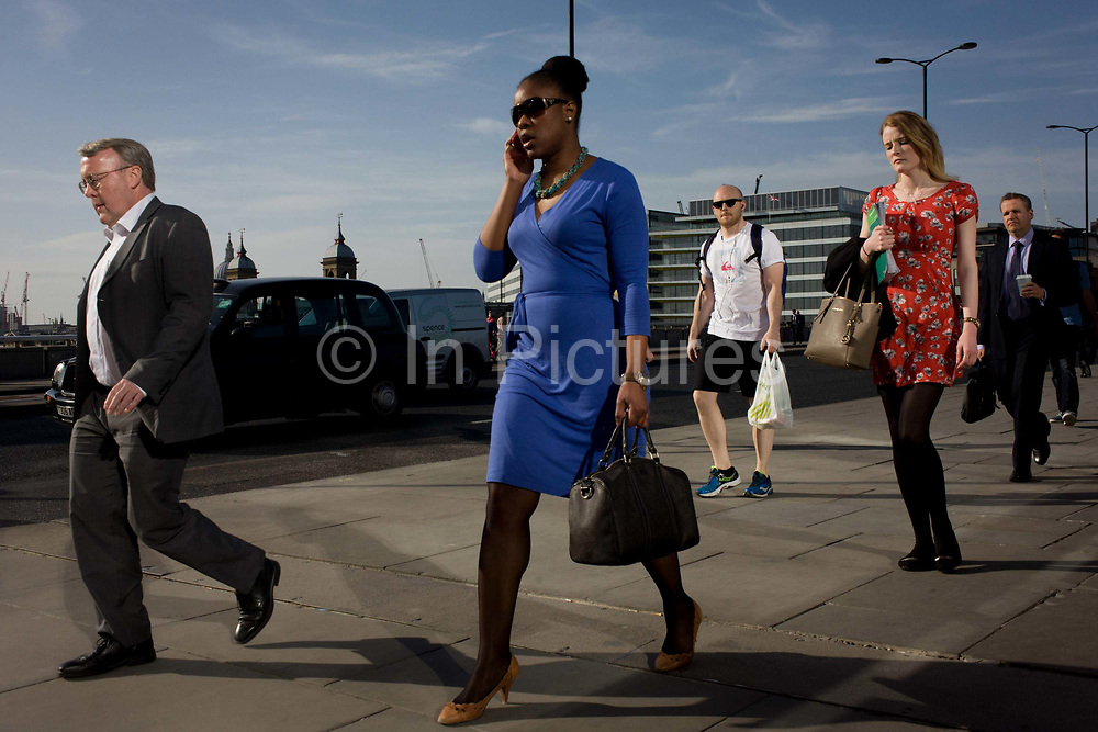 Londoners cross southbound over London Bridge during the evening rush hour. A young black woman wearing a blue dress strides along with a handset to his ear, followed by others walking out of the City of London. There has been a crossing over the Thames here since the Romans first forded the river in the early 1st Century with subsequent medieval and Victorian stone bridges becoming an important thoroughfare from the City on the north bank, to Southwark on the south where transport hubs such as the mainline station gets commuters to the suburbs and satellite towns.