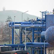 Nederland Barendrecht 29 november 2008 20081129 Foto: David Rozing ..TOT 6 DECEMBER GEEN PUBLICATIE VAN DEZE BEELDEN ..Serie demonstratie project ondergrondse Co2 opslag Shell Barendrecht .NAM in Barendrecht. Op het terrein staat een gaswinninginstallatie, hiermee wordt het gas dat zich onder Barendrecht bevindt naar boven gehaald. Zodra de 2 gasvelden leeg zijn zullen deze waarschijnlijk gebruikt gaan worden voor de ondergrondse opslag van CO2. Dit gebeurt met dezelfde installatie. ..Shell Nederland Raffinaderij B.V. (SNR) heeft het initiatief genomen voor een demonstratieproject in samenwerking met Nederlandse Aardolie Maatschappij ( NAM ). Daarbij is het de bedoeling dat pure CO2 die bij de raffinaderij in Pernis bij de productie van waterstof vrijkomt, per pijpleiding naar Barendrecht wordt getransporteerd. Vervolgens wordt de CO2 in lege aardgasvelden geïnjecteerd voor permanente opslag..OCAP?De Shell exploiteert momenteel de nu nog deels gevulde aardgasvelden Barendrecht en Ziedewij en heeft een grote kennis van de ondergrond en injectie van aardgas in bestaande velden.Het is de bedoeling dat OCAP ook het transport van CO2 naar Barendrecht gaat verzorgen..Shell CO2 Storage B.V.?Voor het project is een nieuw bedrijf opgericht, Shell CO2 Storage B.V. (SCS). SCS zal verder ook zekerstellen dat alle aanwezige kennis over de Barendrechtse velden ten volle kan worden benut bij de opslag van CO2 en de daaraan gekoppelde monitoring.Het Barendrecht-veld?Shell en OCAP hebben net zoals andere organisaties veel onderzoek gedaan naar het transport naar en de mogelijke CO2-opslag in lege aardgasvelden. Vanwege de ligging, dichtbij de CO2-bron van Pernis, hebben de partijen uiteindelijk gekozen voor het aardgasveld Barendrecht (ten zuidwesten van Rotterdam). Als de ervaringen met het Barendrecht-veld goed zijn, zal in een later stadium Barendrecht Ziedewij het tweede veld zijn dat in aanmerking komt voor CO2-opslag. Uit deze aardgasvelden wordt nu nog gas gewonnen. Zodra de