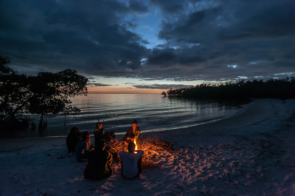 A group sits around a campfire on Lulu Key in the Florida Everglades