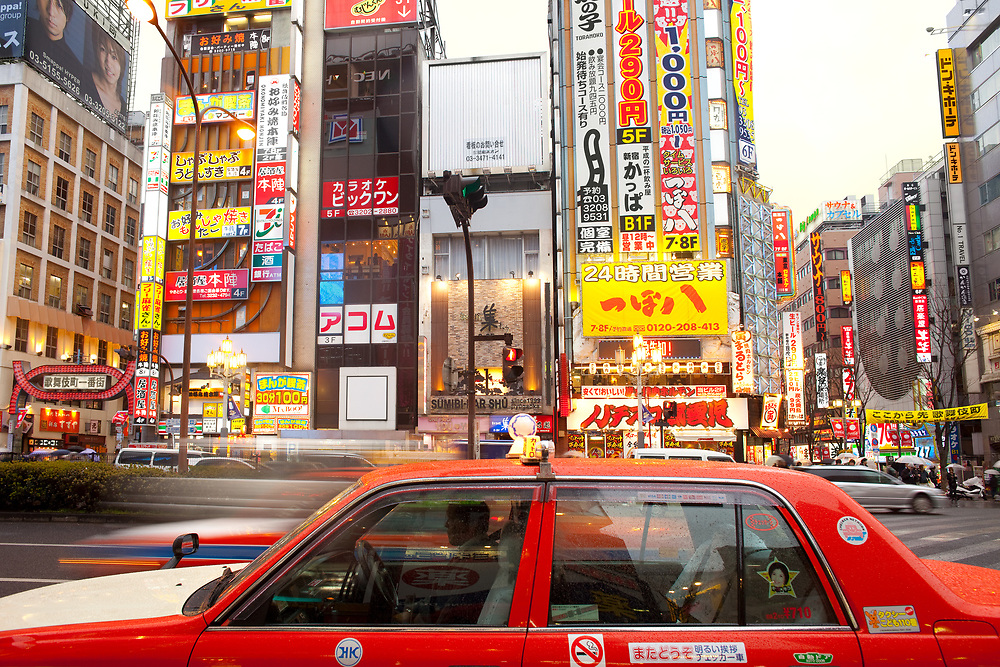 Shinjuku, Tokyo, Kanto Region, Honshu, Japan - April 16, 2010: A red taxi in the bustling district of Shinjuku with advertising signs.