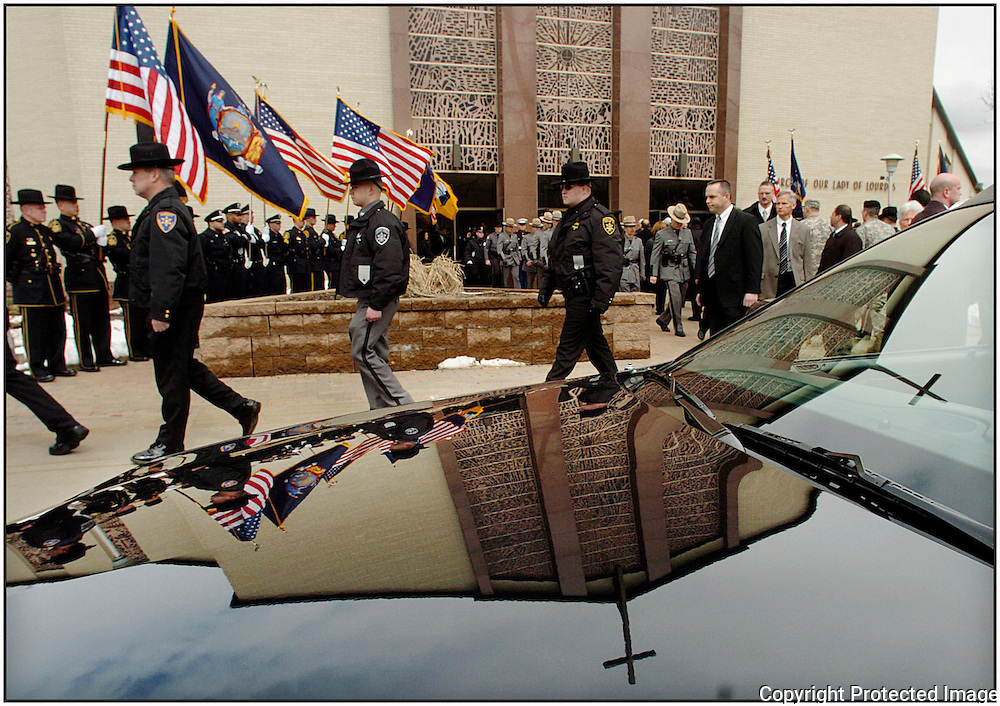 The cross atop the Church of Our Lady of Lourdes Church is seen reflected in the front of the hearse used to carry slain Utica police Officer Thomas Lindsey in Lindsey's funeral,