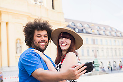 Couple taking selfie using mobile camera in front of Theatiner Church, Munich, Germany