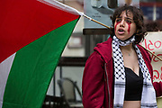 An activist from Palestine Action daubed in fake blood holds a Palestinian flag during a protest outside the UK headquarters of Elbit Systems, an Israel-based company developing technologies used for military applications including drones, precision guidance, surveillance and intruder-detection systems, on 28th May 2021 in London, United Kingdom. Pro-Palestinian activists had organised the protest against Elbits presence in the UK and against British arms sales to and support for Israel.