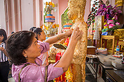 12 OCTOBER 2012 - NAKHON PATHOM, NAKHON PATHOM, THAILAND:     A woman applies gold leaf to a Buddha statue to make merit at Phra Pathom Chedi in Nakhon Pathom. The Phra Pathom Chedi in Nakhon Pathom was commissioned by King Mongkut and completed by King Chulalongkorn in 1870. The chedi is 127 meters tall and is one of the tallest pagodas in the world. It is located in the center of the city of Nakhon Pathom and has been an important Buddhist center since the 6th century. According to local history, Nakhon Pathom is where Buddhism first came to Thailand.   PHOTO BY JACK KURTZ