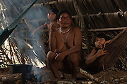 Huaorani Indian, Dete Ikeka burning the hair off of a peccary before cutting it up to either boil or smoke it.<br /> Bameno Community. Yasuni National Park.<br /> Amazon rainforest, ECUADOR.  South America<br /> This Indian tribe were basically uncontacted until 1956 when missionaries from the Summer Institute of Linguistics made contact with them. However there are still some groups from the tribe that remain uncontacted.  They are known as the Tagaeri & Taromenane. Traditionally these Indians were very hostile and killed many people who tried to enter into their territory. Their territory is in the Yasuni National Park which is now also being exploited for oil.