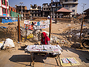 05 MARCH 2017 - KATHMANDU, NEPAL: A woman sells Nepali newspaper in front of Kasthamandap, a Hindu temple destroyed in the 2015 earthquake. Nothing is left of the temple, which was built in the 12 Century. Much of Kathmandu is now a construction site because of rebuilding  two years after the earthquake of 25 April 2015 that devastated Nepal. In some villages in the Kathmandu valley workers are working by hand to remove ruble and dig out destroyed buildings. About 9,000 people were killed and another 22,000 injured by the earthquake. The epicenter of the earthquake was east of the Gorka district.     PHOTO BY JACK KURTZ