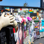 A security officer wears rubber gloves as she protects the Pulse Nightclub memorial on Monday, March 30, 2020 in Orlando, Florida. Visitation has fallen at the site as the Coronavirus (Covid-19) threat has increased. (Alex Menendez via AP)