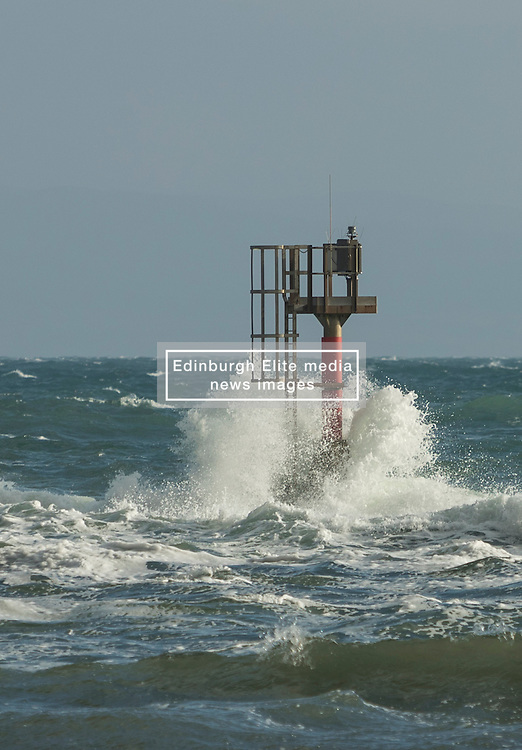 Strong winds hit the West Coast of Scotland. The ferries between the Southern Hebrides and the Scottish mainland have been cancelled as Easterly winds in excess of 40mph make the crossing impossible.<br /> <br /> Pictured: The navigation mast at the entrance into the harbour in Craighouse, Jura is battered by waves.