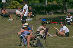 © Licensed to London News Pictures. 23/06/2020. London, UK. Members of public are seen resting in the sun in Victoria Park, east London. Key to easing the lockdown in England will be the two-meter rule - the distance people should stay apart to stop catching coronavirus. Photo credit: Marcin Nowak/LNP
