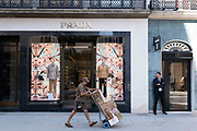 Security guard outside the Prada shop on Bond Street as a UPS delivery woman passes pushing a hand truck of parcels on 26th June 2020 in London, United Kingdom. Bond Street is one of the principal streets in the West End shopping district and is very upmarket. It has been a fashionable shopping street since the 18th century. The rich and wealthy shop here mostly for high end fashion and jewellery.