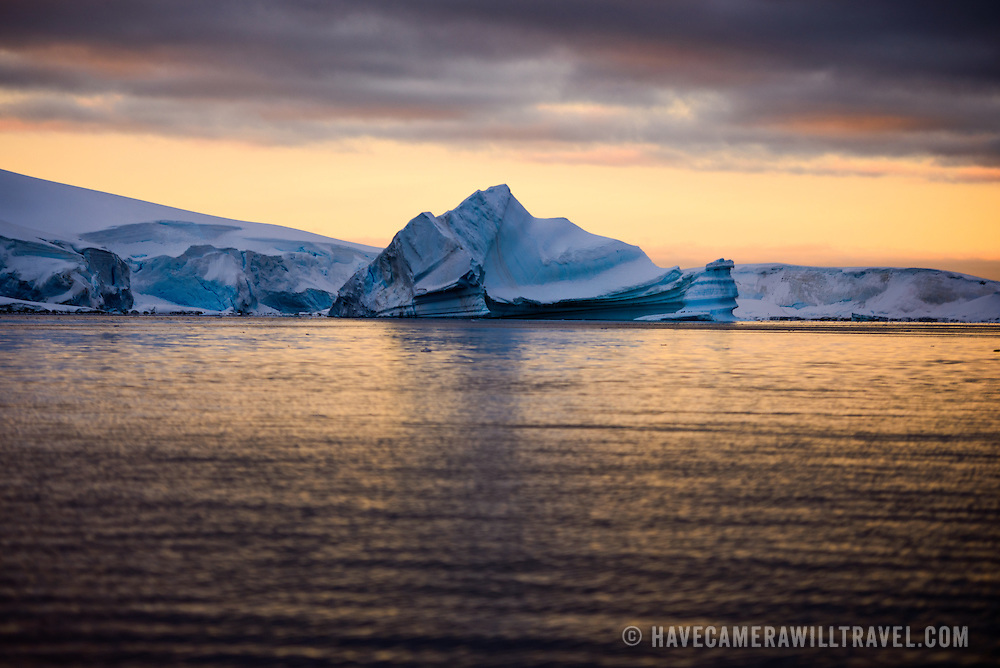 An iceberg stands out against the colors of the setting sun in Hughes Bay in Antarctica.