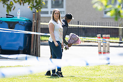 © Licensed to London News Pictures. 28/05/2018. Stockport, UK. A woman and a man carry flowers to the scene outside The Salisbury Club on Truro Avenue in the Brinnington area of Stockport, Greater Manchester, where a car collided with pedestrians late last night, killing one man and injuring others.  A murder investigation has been launched. Police later recovered a black Audi A4 which fled the scene. Photo credit: Joel Goodman/LNP