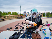 18 MAY 2020 - DES MOINES, IOWA: HEAVEN CHAMBERLIN sprays disinfectant into shoes donated for a memorial in front of the Iowa state capitol in Des Moines. Each Pair Iowa put together a memorial of empty shoes to represent Iowans killed by the COVID-19 pandemic. The memorial is traveling around the state. As of May 18, 355 people in Iowa have died from COVID-19, the disease caused by the Coronavirus (SARS-CoV-2), and 14,955 have tested positive for the Coronavirus.        PHOTO BY JACK KURTZ