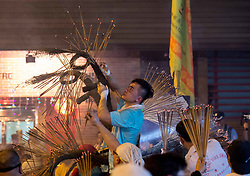 October 3, 2017 - Hong Kong, Hong Kong, China - Participants cover the dragon with freshly lit joss sticks..The annual Tai Hang Fire Dragon Dance welcomes in this years mid-autumn festival..The century old festival, now listed as one of Hong Kong's intangible cultural experiences, sees a 67-metre-long dragon, containing over 70,000 incense sticks carried by performers through the narrow streets. Drummers and other performers to entertain the crowds while the fire dragon scares off evil spirits. (Credit Image: © Jayne Russell via ZUMA Wire)