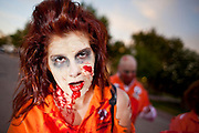 """Oct. 30, 2009 -- PHOENIX, AZ: ASHLEY ATLER leads the Zombies through downtown Phoenix Friday night. About 200 people participated in the first """"Zombie Walk"""" in Phoenix, AZ, Friday night. The Zombies walked through downtown Phoenix """"attacking"""" willing victims and mixing with folks going to the theatre and downtown sports venues.  Photo by Jack Kurtz"""