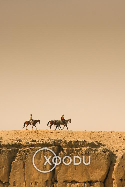 Horses riding along rockface at Giza, Cairo, Egypt (December 2007)