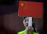A young Chinese woman holds her national flag at a community sporting event in Tongling city in Anhui Province.