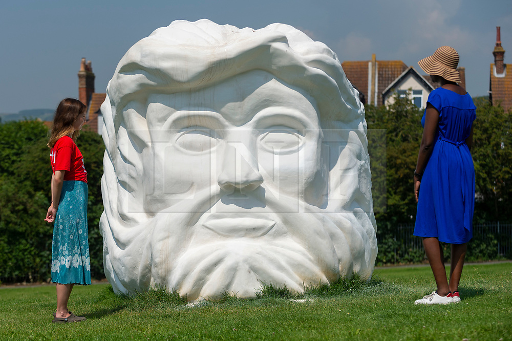 """© Licensed to London News Pictures. 20/07/2021. FOLKESTONE, UK. Women view """"Janus' Fortress: Folkestone"""", 2021, by Pilar Quinteros, a monumental sculptural head sited on a cliff top. Preview of The Plot exhibition, the fifth Creative Folkestone Triennial. Folkestone has no publicly subsidised art gallery, so artists were invited to use public spaces to create new artworks in the seaside town. Over 20 works by artists including Assemble, Rana Begum, Gilbert & George, Atta Kwami, Pilar Quinteros, and Richard Deacon are on display 22 July to 2 November 2021.  Photo credit: Stephen Chung/LNP"""