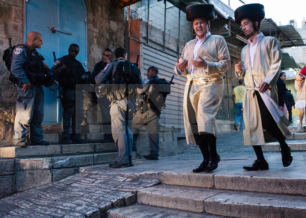 © Licensed to London News Pictures. 02/05/2014. Jerusalem, Israel. Young jewish men hurry past armed police through the Muslim Quarter of the Old City of Jerusalem at approx 6.30pm in order to reach The Western Wall  in time for the start of the Shabbat (the Jewish sabbath).  Jewish custom sees the lighting of candles scheduled for 6.39pm this evening, shortly before the sunset when Shabbat commences.  The Western Wall is the most important shrine of the Jewish faith and is located in the Old City at the foot of the western side of Temple Mount.  The Old City is comprised of four Quarters - the Jewish, Muslim, Christian and Armenian. Photo credit : Richard Isaac/LNP