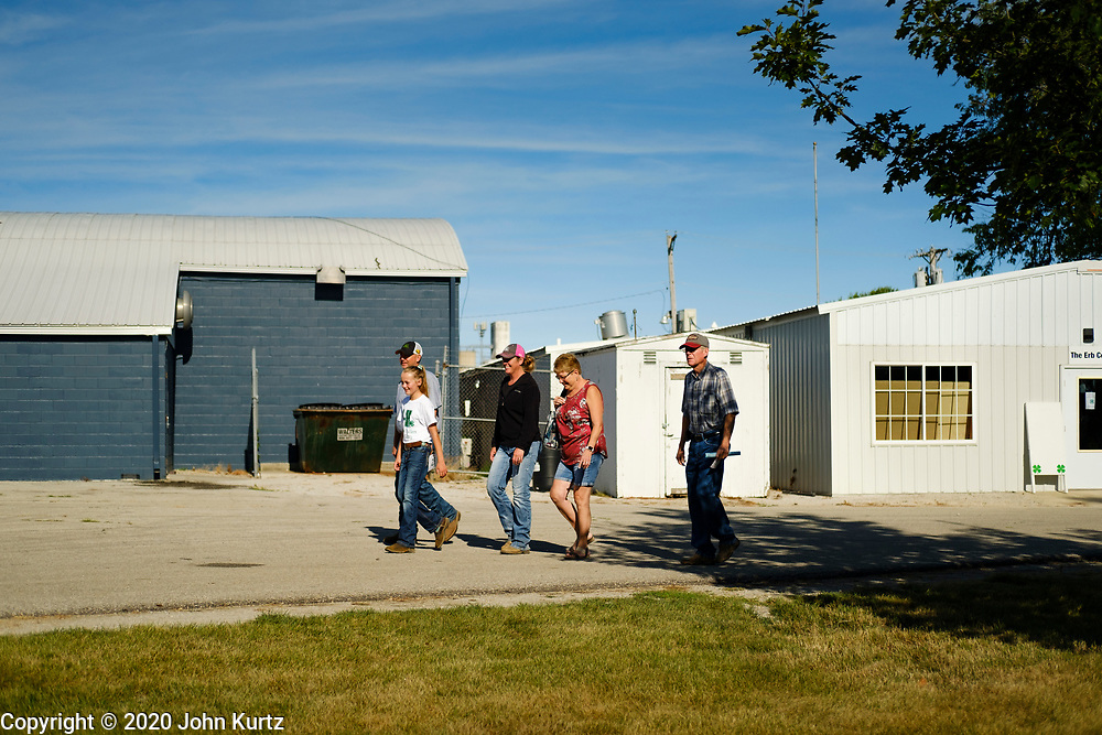 16 JULY 2020 - BOONE, IOWA: A family walks the mostly closed fairgrounds on the first day of the Boone County Fair in Boone. Summer is county fair season in Iowa. Most of Iowa's 99 counties host their county fairs before the Iowa State Fair. In 2020, because of the COVID-19 (Coronavirus) pandemic, many county fairs were cancelled, and most of the other county fairs were scaled back to concentrate on 4H livestock judging. Boone county scaled back its fair this year. The Iowa State Fair was cancelled completely. Boone County Emergency Management did not approve going ahead with the fair, and has advised anyone who goes to the fair to take precautions and monitor themselves for symptoms of the Coronavirus.            PHOTO BY JACK KURTZ