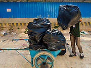 "15 FEBRUARY 2019 - SIHANOUKVILLE, CAMBODIA: A Cambodian laborer hauls garbage away from a casino in Sihanoukville. There are about 80 Chinese casinos and resort hotels open in Sihanoukville and dozens more under construction. The casinos are changing the city, once a sleepy port on Southeast Asia's ""backpacker trail"" into a booming city. The change is coming with a cost though. Many Cambodian residents of Sihanoukville  have lost their homes to make way for the casinos and the jobs are going to Chinese workers, brought in to build casinos and work in the casinos.       PHOTO BY JACK KURTZ"