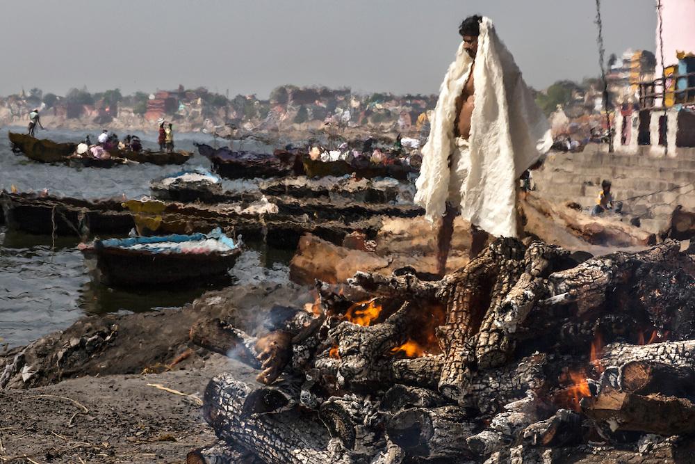 Vêtu d'une tunique blanche, le fils du du défunt attend que la crémation soit achevée