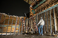 """Renovation work done by Bonnette, Page and Stone at the Colonial Theater in downtown Laconia.  Bob Ferguson of in the upper balcony stage works to uncover the centerpiece showing the year """"1914"""".   ©2016 Karen Bobotas Photographer"""