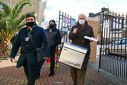 © Licensed to London News Pictures. 13/03/2021. London, UK. A man carrying a freezer box which contains Oxford AstraZeneca Covid-19 vaccines arrives at the London Islamic Cultural Society and Mosque also known as Wightman Road Mosque, in Haringey, north London. The Mosque is working in partnership with Federated4Health, and is encouraging local communities to be inoculated. These include local Muslim communities, where there is reported to be low take-up of the coronavirus vaccine.<br /> <br /> ***Permission Granted***<br /> <br /> Photo credit: Dinendra Haria/LNP