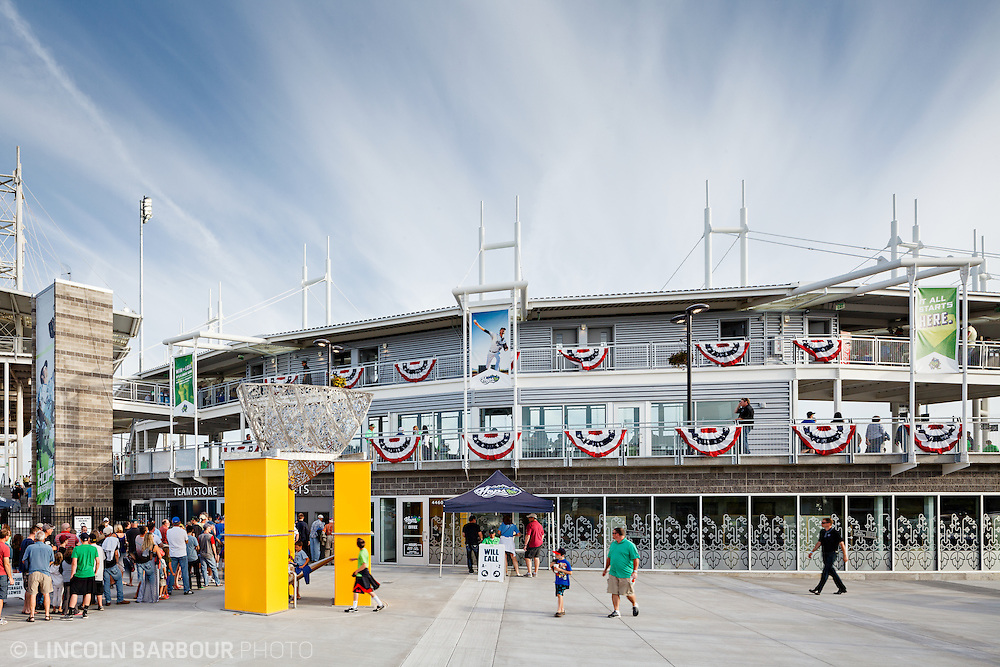 From the outside, fans are lining up to enter a minor league baseball stadium for the afternoon's game on a beautiful day.