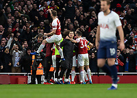 Football - 2018 / 2019 Premier League - Arsenal vs. Tottenham Hotspur<br /> <br /> Shkodran Mustafi (Arsenal FC) leaps into the air as his team mates congratulate Pierre-Emerick Aubameyang (Arsenal FC) after scoring the equaliser at The Emirates.<br /> <br /> COLORSPORT/DANIEL BEARHAM