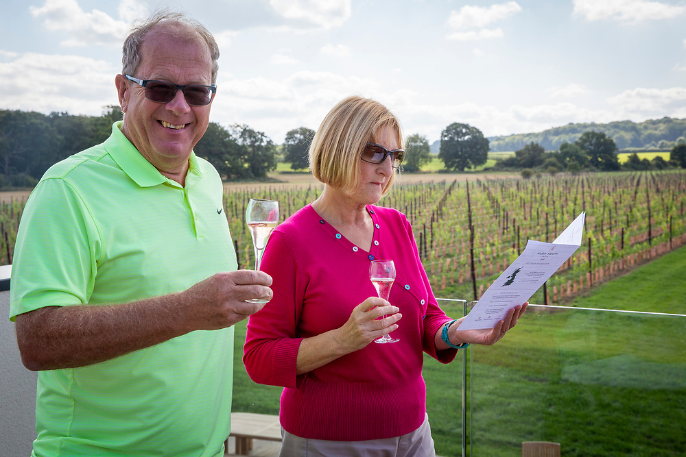 A couple enjoy a glass of wine outdoors after a wine tasting session at Hush Heath Winery, Staplehurst, Kent, England, UK. The woman reads more information about the wine froth winery leaflet.  (photo by Andrew Aitchison / In pictures via Getty Images)