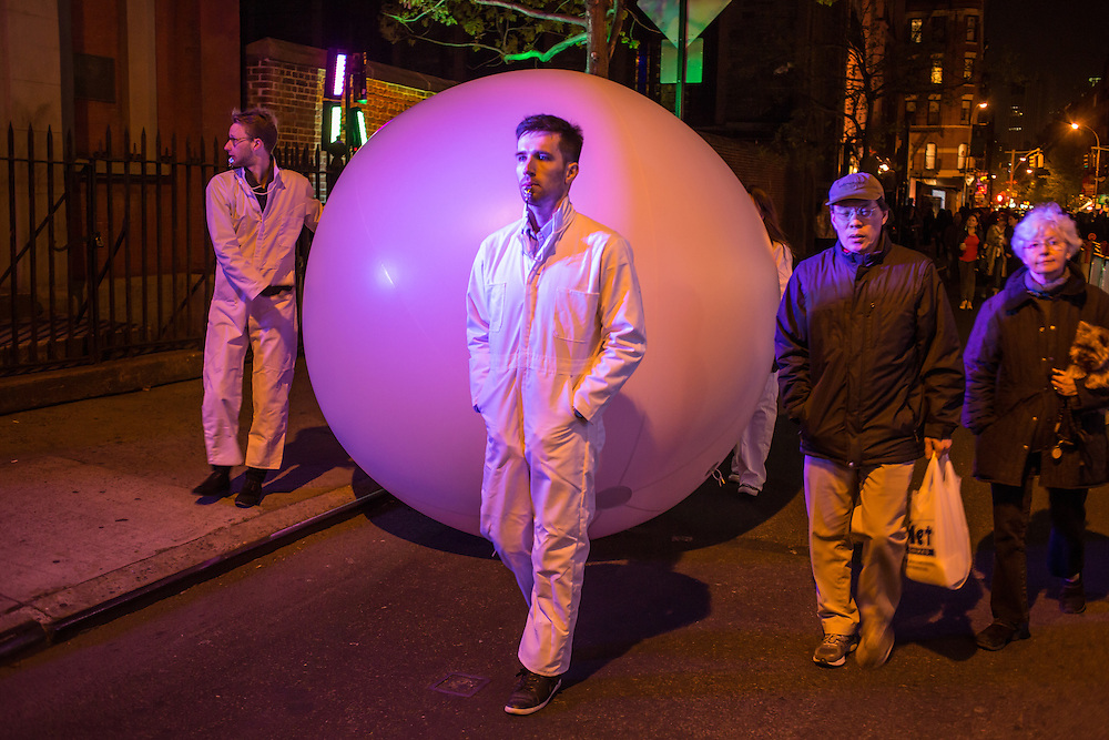 Handlers from Snarkitecture slowly move an inflated ball down Mulberry Street as a performance in the Ideas City festival while two bystanders walk by.