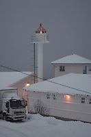 Winter View of the  Finnsnes Lighthouse in a Snowstorm. Image taken with a Nikon D2xs and 85 mm f/1.4 lens (ISO 200, 85 mm, f/1.4, 1/400 sec).