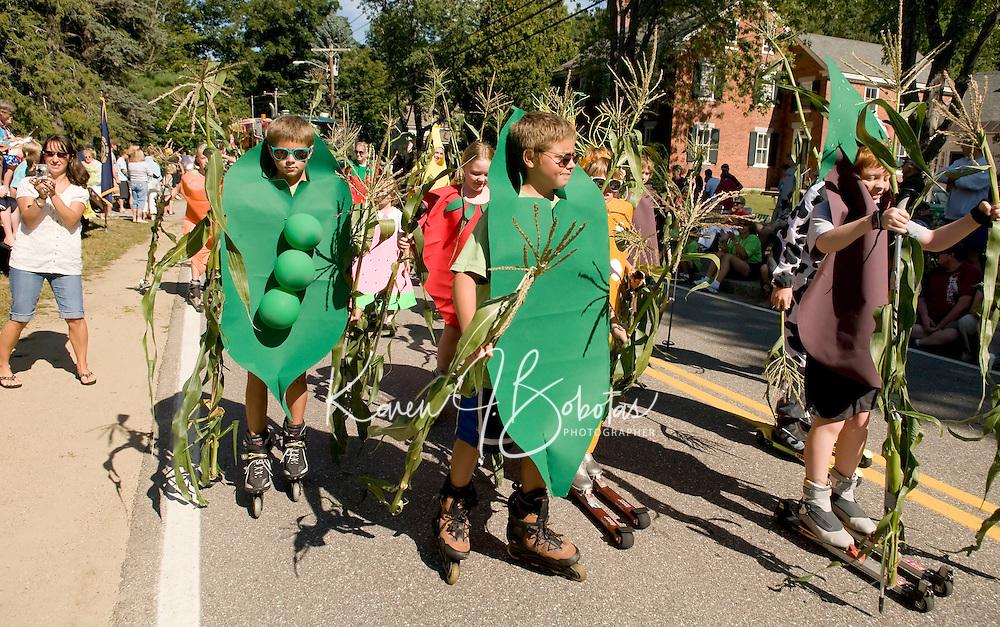 Two peas in a pod Seth and Sander Valpey along with fellow fruits and vegetables from the Gunstock Nordic Association make their way down Belknap Mountain Road on roller blades/skis for the annual Gilford Old Home Day parade Saturday morning.  (Karen Bobotas/for the Laconia Daily Sun)
