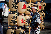 TOKYO, JAPAN, 29 SEPTEMBER  - A group of people coming from Akita prefecture in Tohoku in the north of Japan make a show of Kanto Festival in the square of Yurakucho - Ginza. A Kanto is a pbamboo structure that maintain 46 paper lanterns and can be over 60 kg. It become higher an higher as performance when they add new Kanto pieces . Young people with short jacket kimono, head band hachimachi, white socks tabi and Zori straw sandals take turns to support the O-waka - full structure - on the shoulders, their forheads or their hips - September 2012