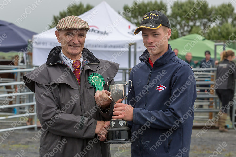 Sam Milligan presents the cup to Kieran Killeen from Mullagh, winner of the overall Dairy Champion, in the  2018 Mullagh Horse and Cattle show