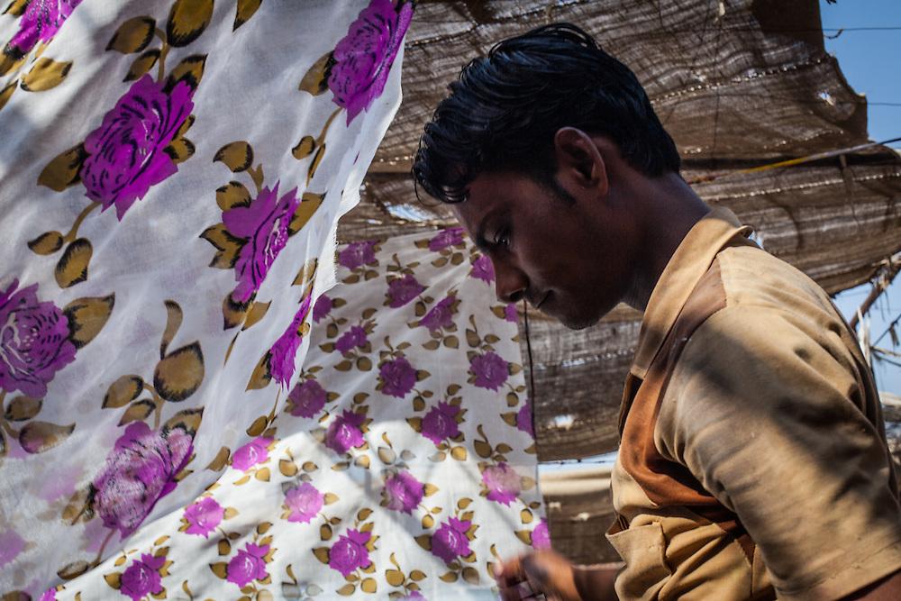 A young worker walks between hanging Sari material.