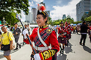 "15 JUNE 2014 - BANGKOK, THAILAND:  A Thai bagpipe band marches through Lumpini Park in Bangkok during a ""Return Happiness to Thais"" party Sunday. The Thai military junta, formally called the National Council for Peace and Order (NCPO), is sponsoring a series of events throughout Thailand to restore ""Happiness to Thais."" The events feature live music, dancing girls, military and police choirs, health screenings and free food.  PHOTO BY JACK KURTZ"