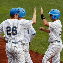 Jun 25, 2013; Omaha, NE, USA; UCLA Bruins center fielder Brian Carroll (right) is congratulated by pitcher David Berg (26) for scoring during the first inning in game 2 of the College World Series finals against the Mississippi State Bulldogs at TD Ameritrade Park. Mandatory Credit: Derick E. Hingle-USA TODAY Sports