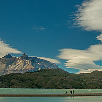 Tourists hike across a sand bar on Grey Lake, below the Horns of Paine in Torres del Paine National Park, Chile.